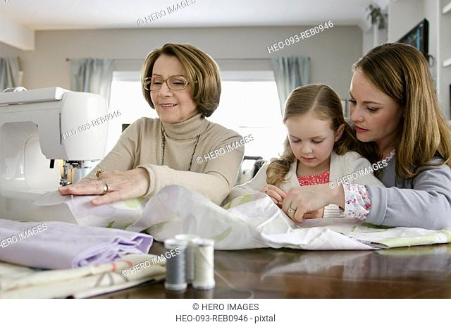 grandmother and mother teaching young girl to sew
