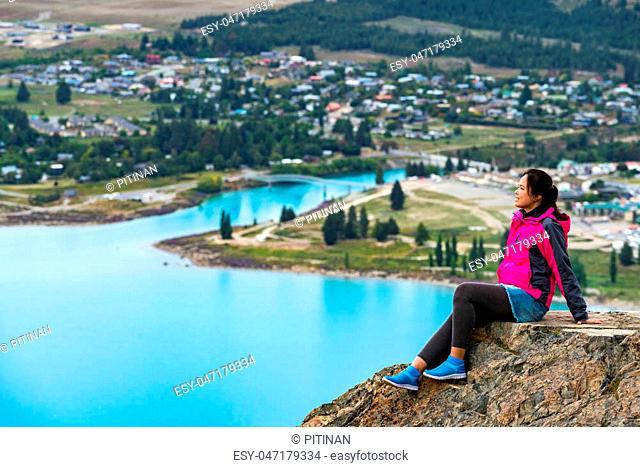 Woman traveller enjoys scenic view of lake Tekapo landscape in New Zealand