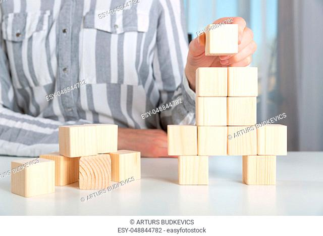 Woman placing last piece to wooden blocks in rocket shape. Start up business launch success concept