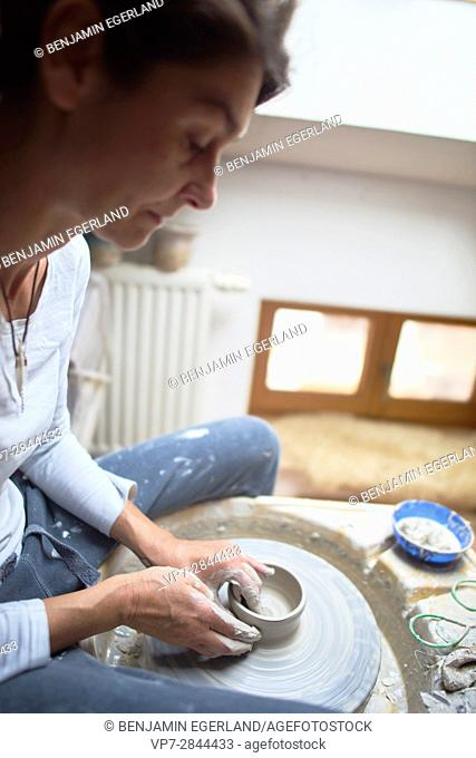 ardent mature woman creating pottery