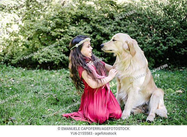 Portrait of little girl with crown of daisies and Golden Retriever dog