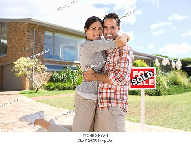 Portrait of smiling couple hugging outside new house