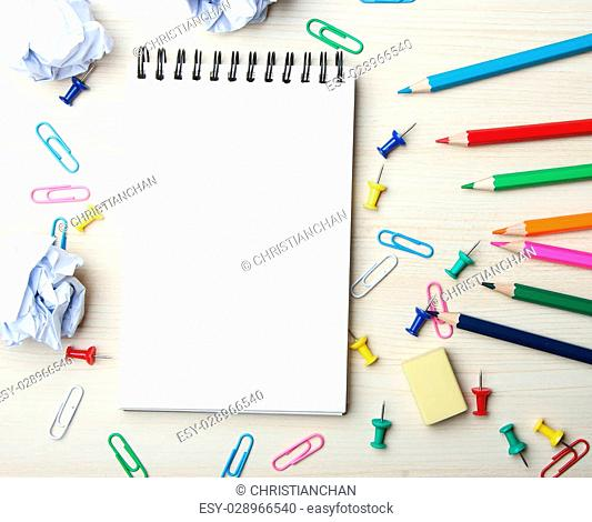 School supplies and blank notebook on the wood desk background