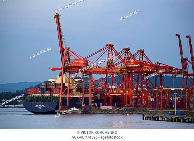 Cranes loading shipping containers on a cargo vessel at Vancover port, British Columbia, Canada