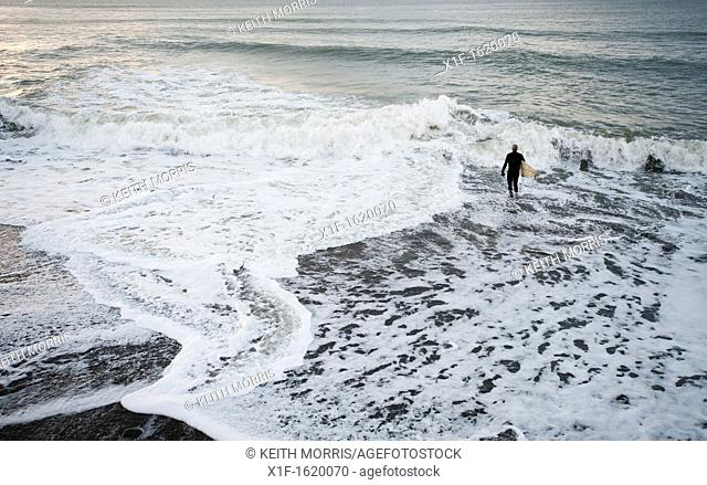 A man about to go surfing in the sea, Aberystwyth, November, Wales UK