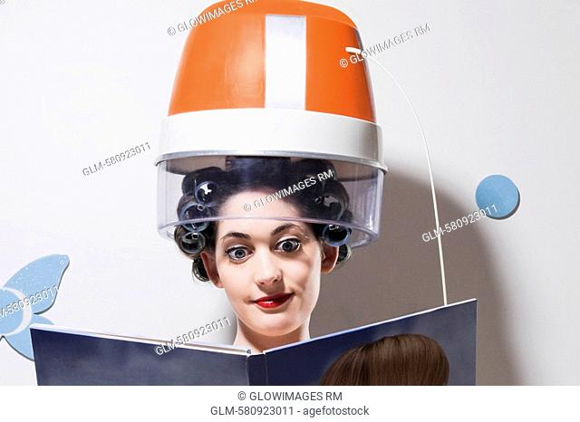 Close-up of a young woman sitting under hair dryer and reading a book