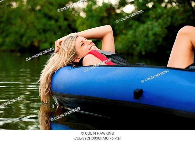 Woman relaxing in kayak in creek