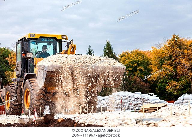 SAMARA, RUSSIA - SEPTEMBER 28, 2014: Heavy bulldozer loading and moving gravel on road construction site