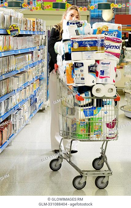 Woman pushing a shopping cart in a supermarket