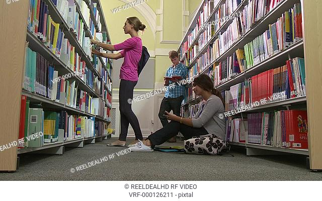 Group of students in library reading and playing with mobile phone
