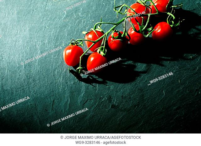 Cherry tomatoes on grey background