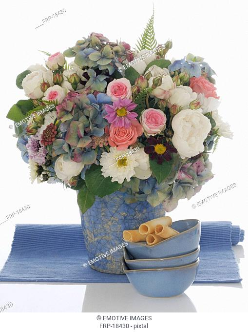 Bunch of flowers in blue vase and and three blue bowls