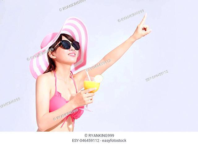 beauty woman wear bikini and take orange juice shoe somrthing to you with isolated gray background, asian