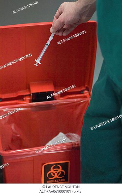 Healthcare professional placing used syringe in hazardous waste receptacle