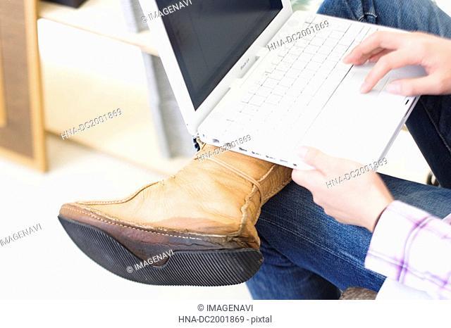 Man Using Laptop On Knee