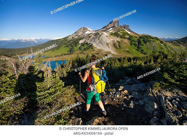 A photographer takes a picture of a young woman backpacking on the Panorama Ridge Trail with Black Tusk Mountain in the background in Garibaldi Provincial Park