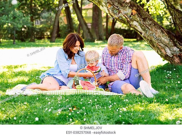 Happy family having a picnic in the park eating a watermelon