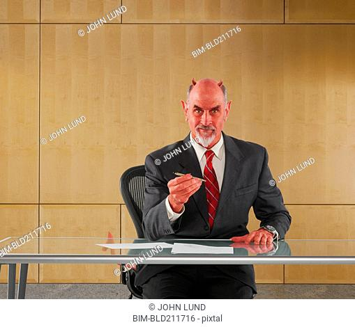 Caucasian businessman in devil costume offering pen to sign contract