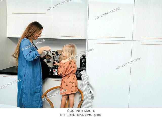 Mother with daughter making coffee