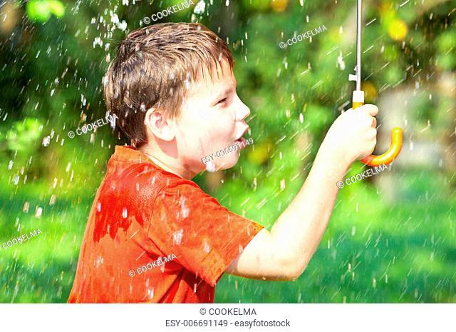 boy under an umbrella during a rain .