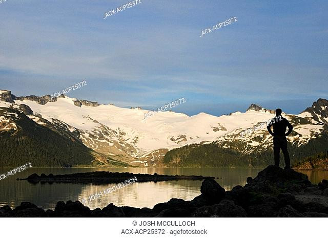 A hiker is silhouetted by the Sphinx Glacier at Garibaldi Lake in Garibaldi Provincial Park near Whistler BC