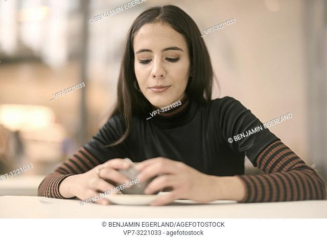 portrait of content woman looking down to coffee cup while enjoying break at table in café, in Munich, Germany