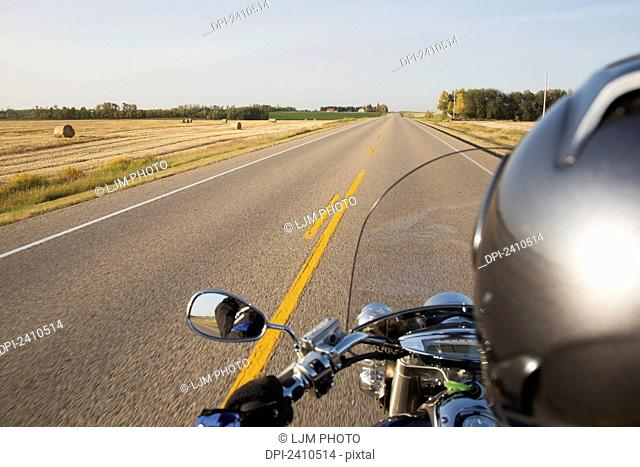 Motorcyclist riding on the highway, near Edmonton; Alberta, Canada