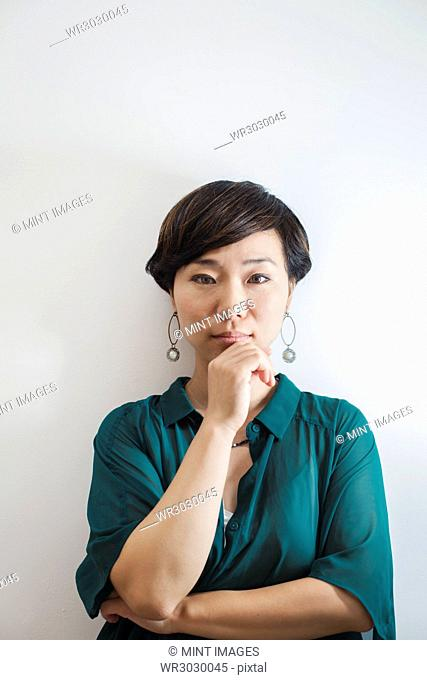 Woman with short black hair wearing green shirt standing in art gallery, hand on chin, looking at camera