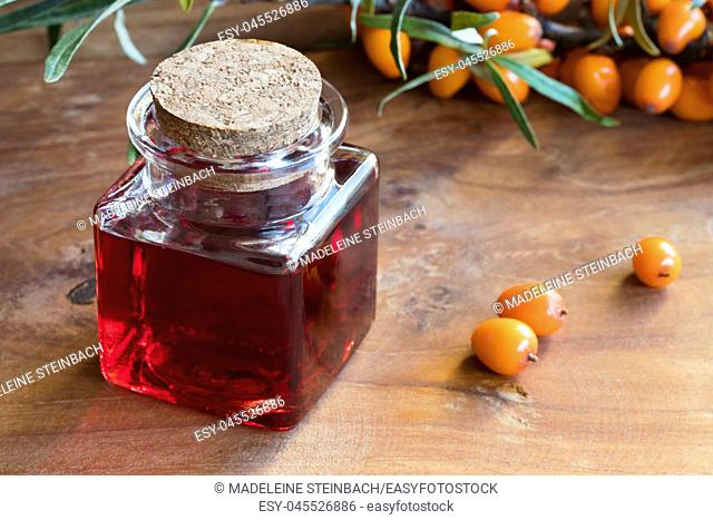 Sea buckthorn oil in a glass jar with sea buckthorn berries and leaves in the background