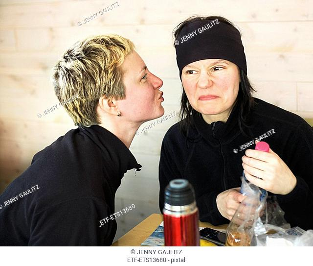 One woman faking a kiss one woman making a face Sweden