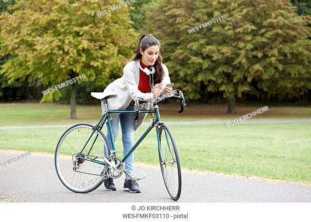 Woman with bicycle in an autumnal park looking at cell phone