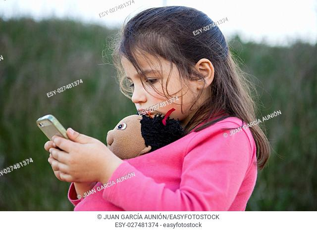 Little girl playing with mobile phone and holding her doll outdoor