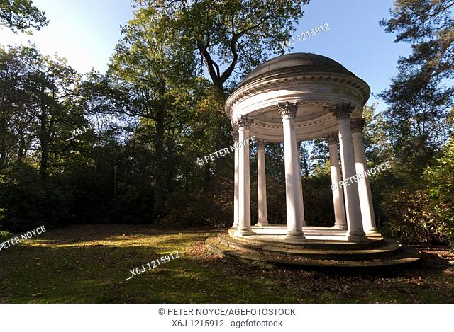 Gazebo of decorated columns pillars in a clearing surrounded by trees