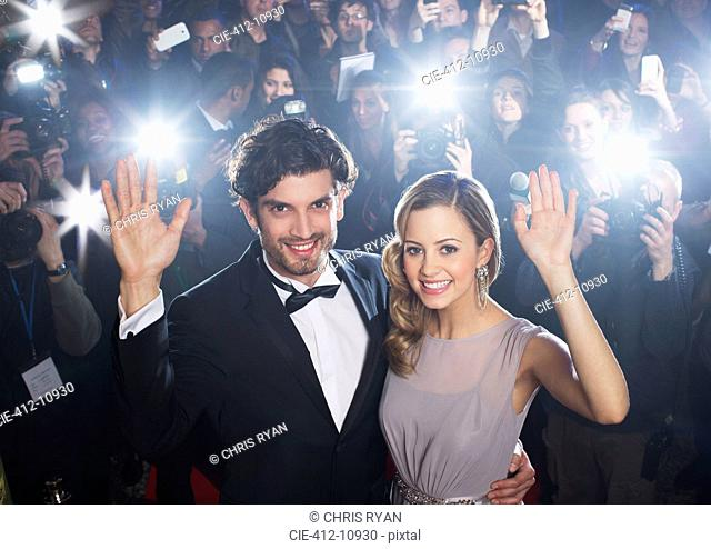 Celebrity couple waving on red carpet with paparazzi in background