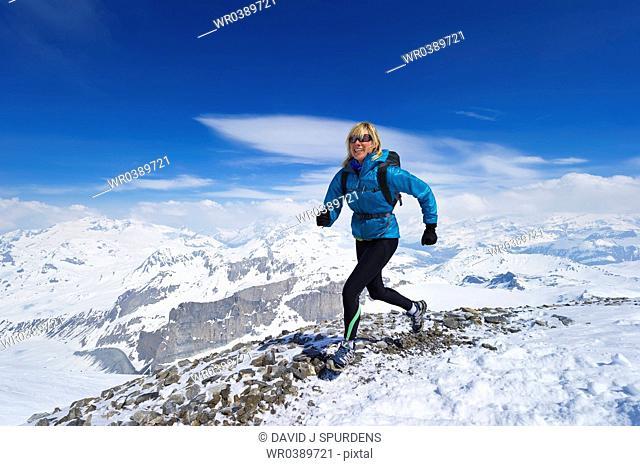 Women smiles as she runs across snowy mountains