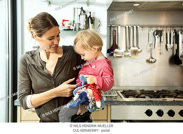 Mother carrying baby girl in kitchen