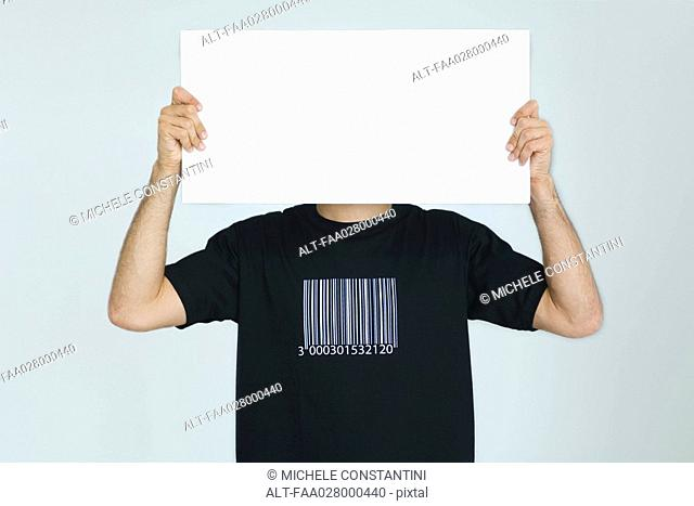 Man wearing tee-shirt with bar code, holding blank sign in front of face