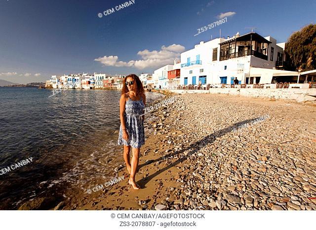 Woman walking at the beach in Little Venice district, Mykonos, Cyclades Islands, Greek Islands, Greece, Europe