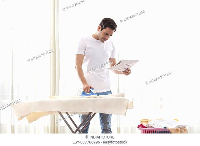 Young man reading newspaper while ironing