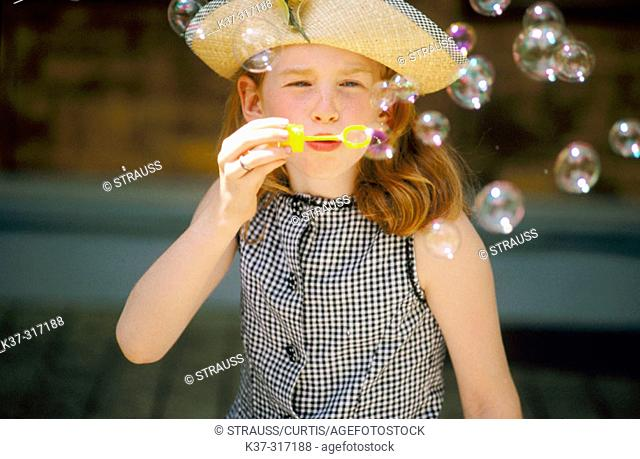 8 years old girl blowing bubbles