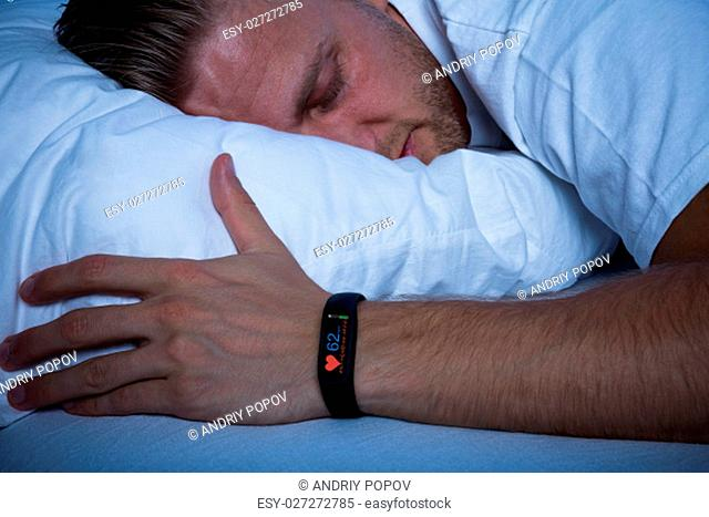 Fitness Activity Tracker With Heartbeat Rate On Man's Hand Over Bed