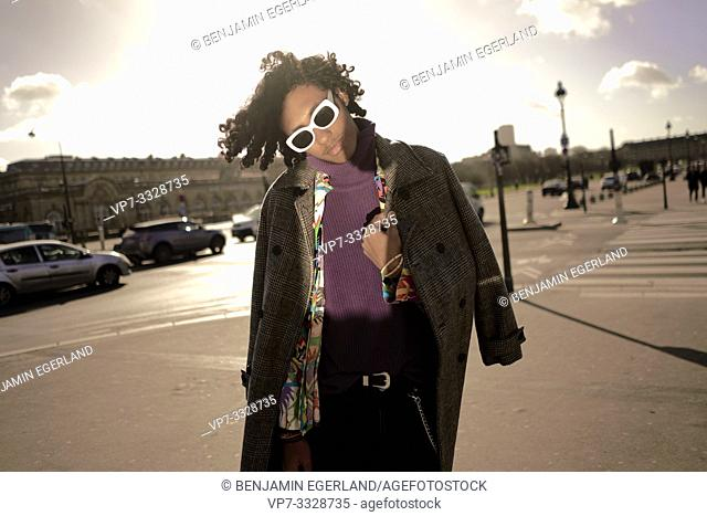young emotive fashion model man at street, in city Paris, France