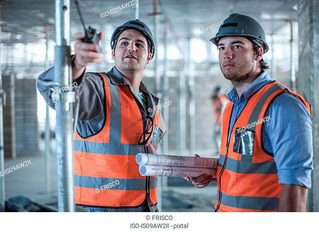 Site manager and builder pointing on construction site