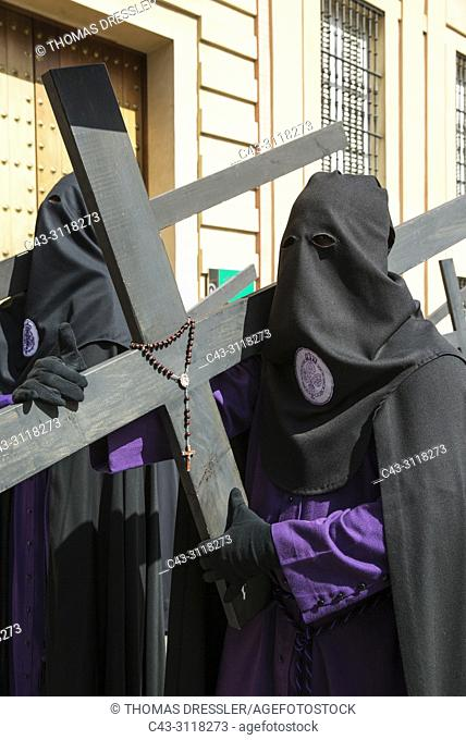 Penitent with cross and rosary at the Semana Santa (Holy Week) of Seville. Seville province, Andalusa, Spain