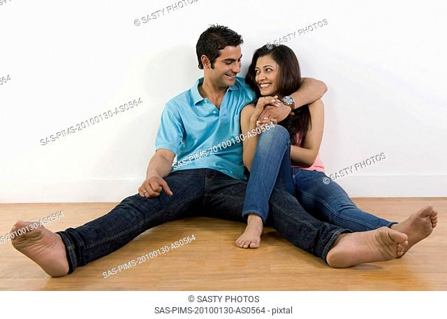 Couple sitting on the floor and smiling