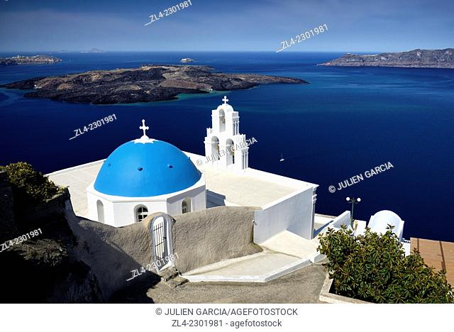 Greek orthodox church with blue dome in the village of Fira overlooking the caldera and the volcanic island of Nea Kameni