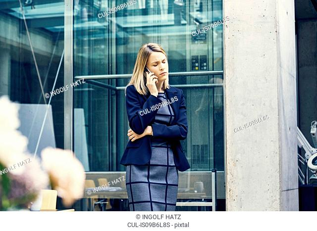 Displeased young businesswoman making smartphone call in open plan office