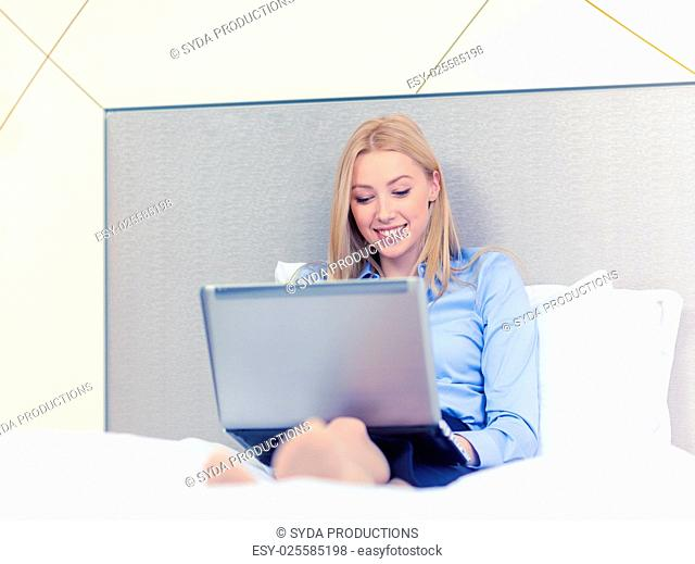 business, technology, internet and hotel concept - happy businesswoman with laptop computer lying in hotel in bed