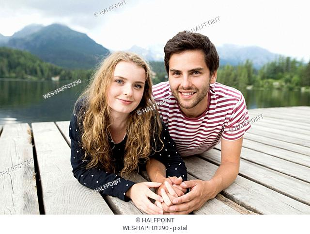 Young couple in love lying on jetty at lake