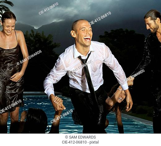 Fully dressed friends playing in swimming pool